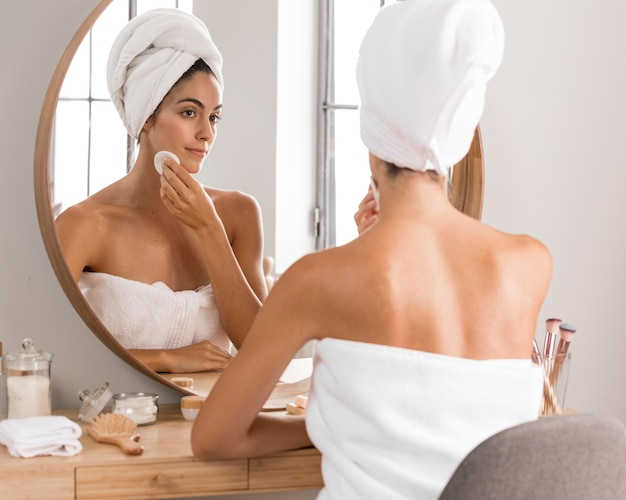 Beautiful young woman using products and looking into the mirror