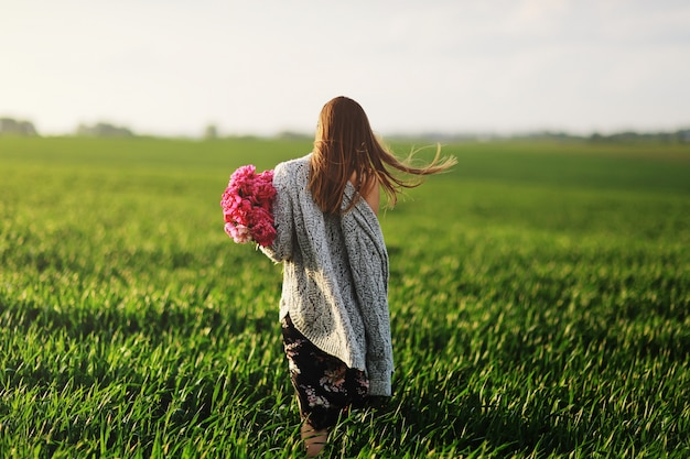 Beautiful young woman on a walk, the girl in flowers. bouquet of peony. elegant young woman with gorgeous hair. a girl with peony walks in the field.