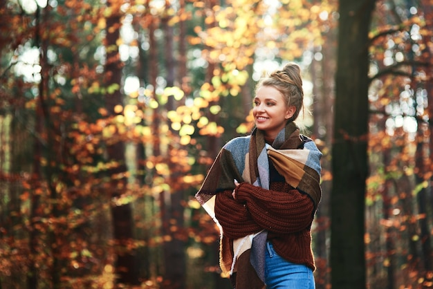 Bella giovane donna che cammina nella foresta autunnale