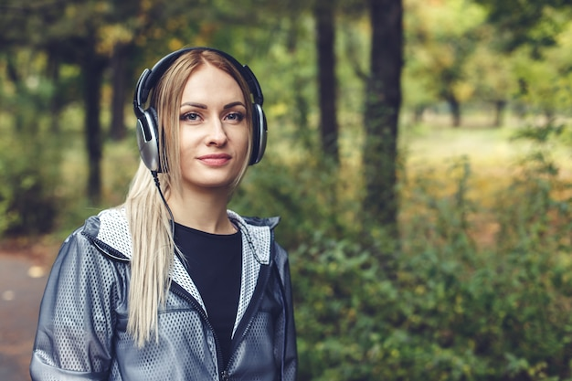 Beautiful young woman walking on city park, listening to music on headphones.
