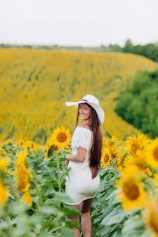 夏に咲くひまわり畑を歩いて美しい若い女性。白いドレスと帽子の長い髪を持つスタイリッシュな女性。夏休み