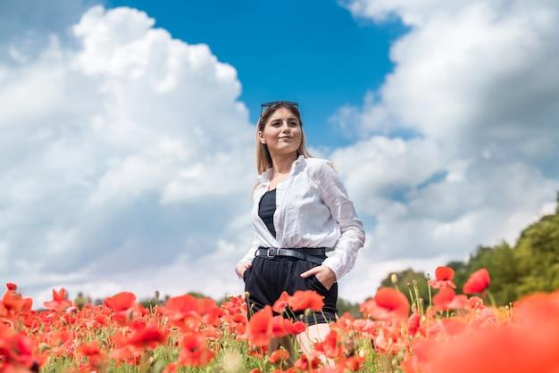 Красивая молодая женщина гуляет в маковом поле в летний день