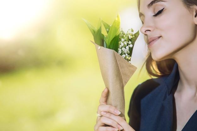 Красивая молодая женщина гуляет в парке с букетом ландышей в руках портрета