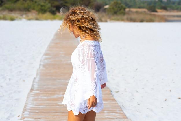 해변에서 모래 위에 보도에 걷는 아름 다운 젊은 여자. 곱슬 머리와 흰색 드레스를 입고 해변의 모래 한가운데 보도에 서 있는 여자. 해변에서 휴가를 보내는 여자