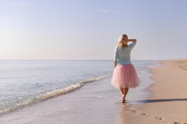 砂浜の海のビーチを歩く美しい若い女性