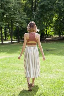 日没時に牧草地で屋外を歩く美しい若い女性。女性の背中。