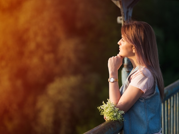 Beautiful young woman walking in the park at sunset with a bouquet of flowers