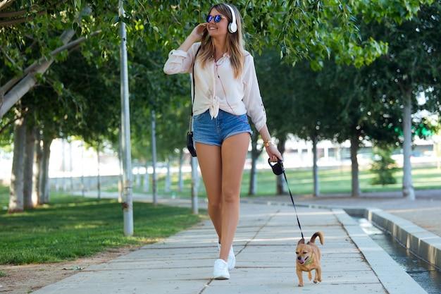 Bella giovane donna che cammina con il suo cane nel parco.