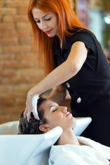 Красивая молодая женщина моет волосы в салоне красоты.
