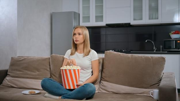 영화를보고 팝콘과 함께 소파에 앉아 아름 다운 젊은 여자.