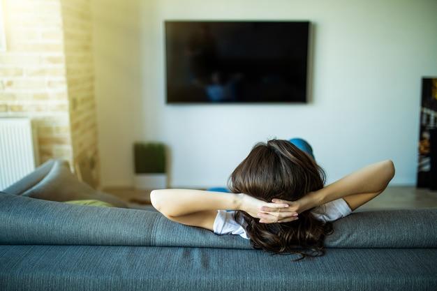 집에서 소파에 앉아 tv를보고 아름 다운 젊은 여자