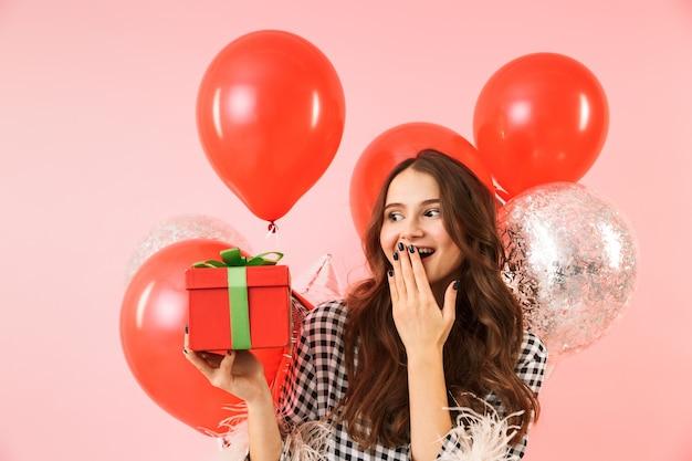 분홍색 배경 위에 절연 재킷 서 입고, 축하, 풍선과 선물 상자의 무리를 들고 아름 다운 젊은 여자