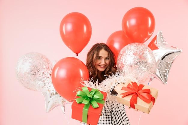 ピンクの背景の上に孤立して立っているジャケットを着て、祝って、風船とプレゼントボックスの束を保持している美しい若い女性