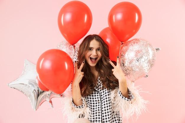 ピンクの背景の上に孤立して立っているジャケットを着て、祝って、風船の束を保持している美しい若い女性