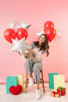 ピンクの背景の上に孤立して立っているジャケットを着て、風船とギフトボックスの束で祝う美しい若い女性