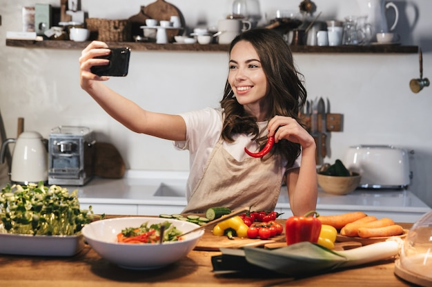 Beautiful young woman wearing apron cooking healthy salad at the kitchen at home, taking a selfie with mobile phone