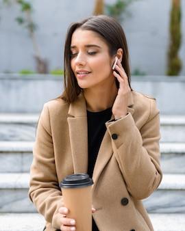 테이크 아웃 커피를 마시는 벤치에 앉아 가을 코트를 입고 아름 다운 젊은 여자