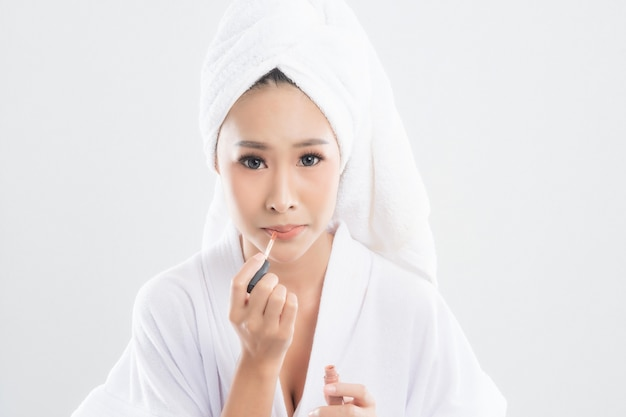 Beautiful young woman wearing bathrobe with towel with towel on head is using lipstick to put on her mouth after finish makeup
