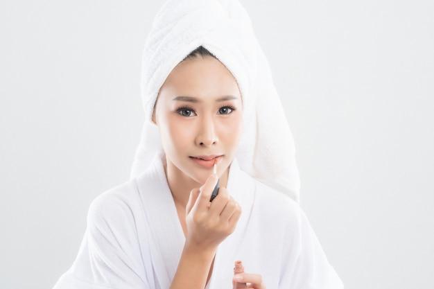 Красивая молодая женщина в халате с полотенцем с полотенцем на голове использует помаду