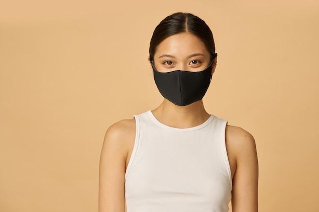 ベージュの上に孤立したポーズをしながらカメラを見て黒い顔のマスクを身に着けている美しい若い女性