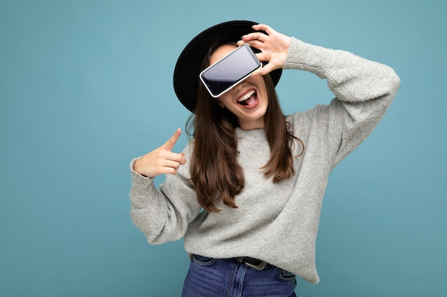 Beautiful young woman wearing black hat and grey sweater holding phone showing smartphone by pointing finger at mobile screen isolated on background