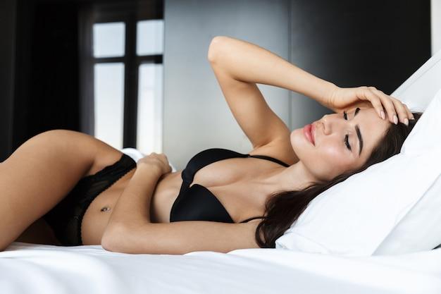 침대에 누워 검은 란제리를 입고 아름 다운 젊은 여자