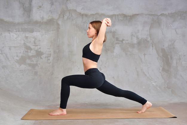 Beautiful young woman wearing black sportswear practicing yoga, standing in warrior one pose,