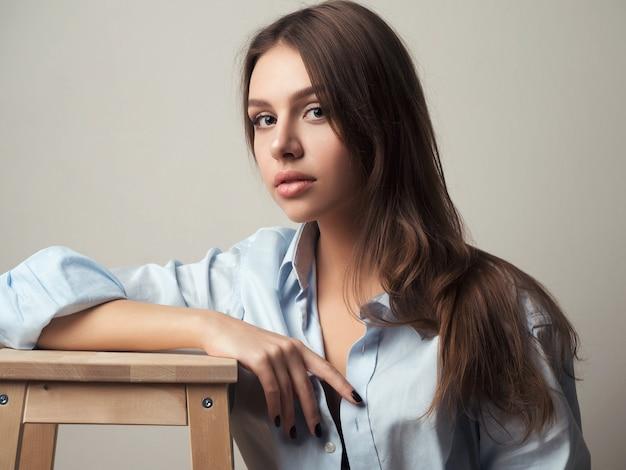 Beautiful young woman wearing blue mens shirt. model sitting on wooden stool.