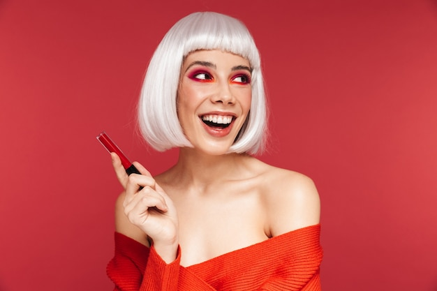 Beautiful young woman wearing bright makeup and white wig standing isolated on pink, holding red lipgloss