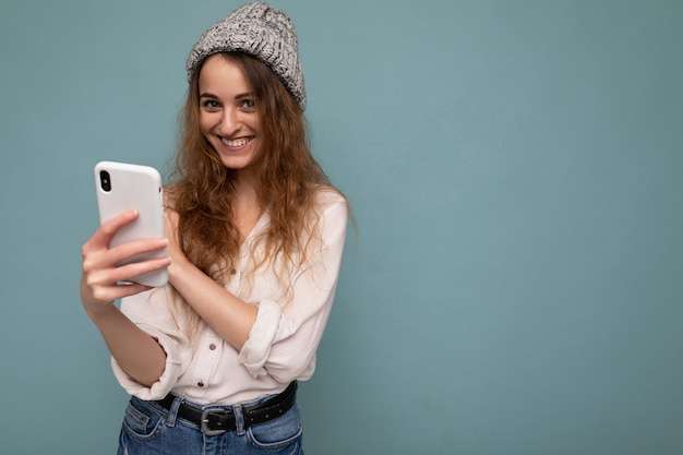 Beautiful young woman wearing casual clothes standing isolated over background surfing on the internet via phone looking at mobile screen.