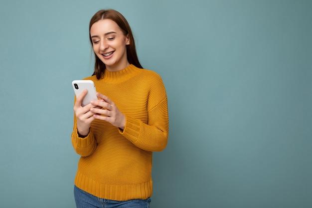 Красивая молодая женщина в повседневной одежде, стоя изолированной над стеной, серфинг в интернете по телефону, глядя на мобильный экран.
