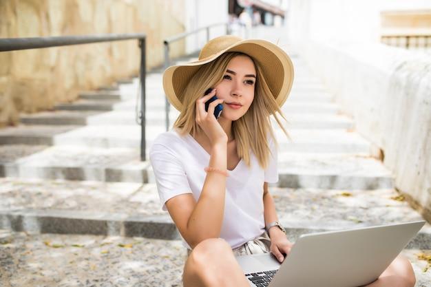 Красивая молодая женщина в повседневном летнем наряде сидит на уличной лестнице