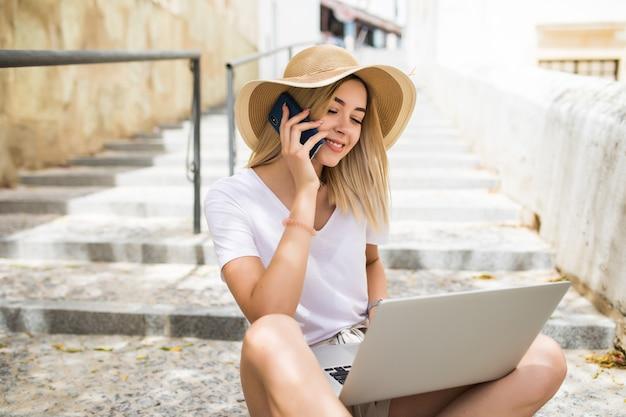 Bella giovane donna che indossa abbigliamento estivo casual seduto sulle scale della strada