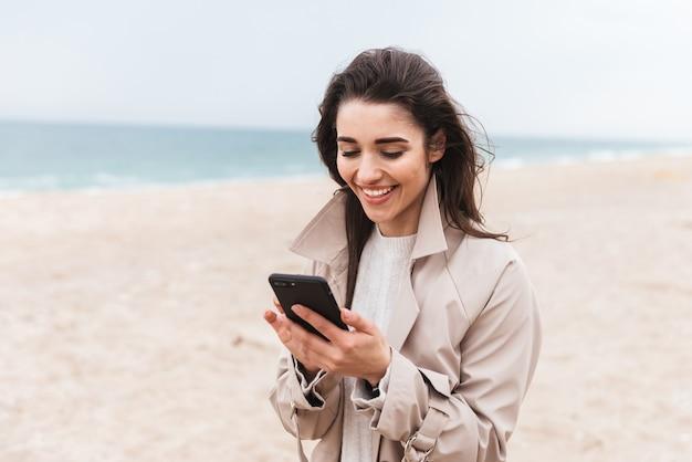 Красивая молодая женщина в пальто гуляет на берегу моря, используя мобильный телефон