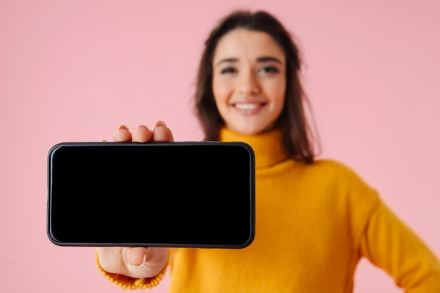 빈 화면 휴대 전화를 보여주는 핑크 이상 격리 서 화려한 옷을 입고 아름 다운 젊은 여자