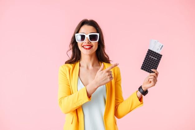 Красивая молодая женщина в яркой одежде стоя изолированно над розовым, показывая паспорт с билетами на самолет