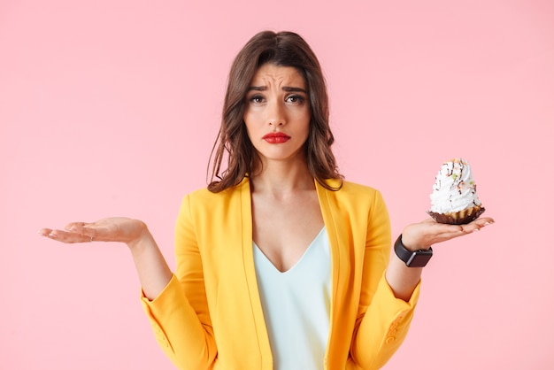 Beautiful young woman wearing colorful clothes standing isolated over pink, holding creamy cupcake