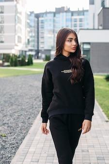 建物を背景に通りを歩きながら快適なトラックスーツを着た美しい若い女性。女性のファッション。都市のライフスタイル