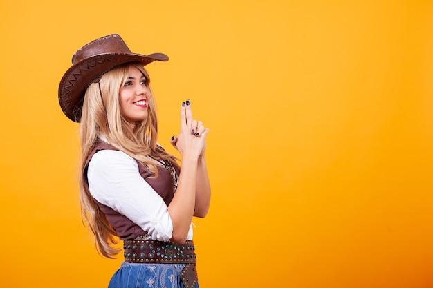 노란색 배경 위에 카우보이 의상을 입고 아름 다운 젊은 여자. 어리석은 순간