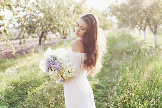 우아한 하얀 드레스를 입고 여름 정원에서 아름다운 화창한 오후를 즐기는 아름다운 젊은 여자