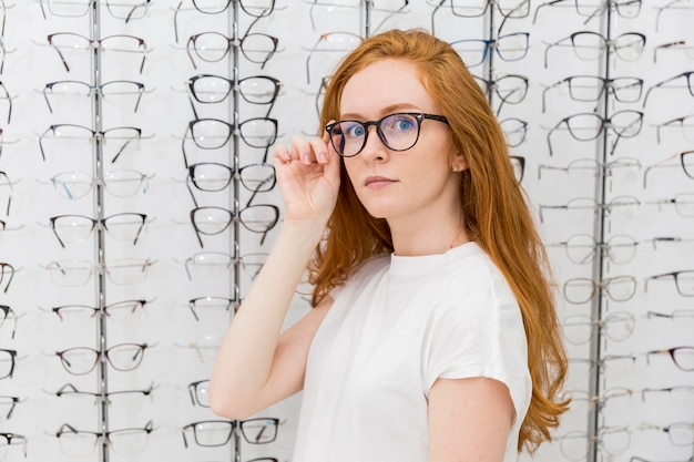 Beautiful young woman wearing eyeglasses looking at camera in optician shop