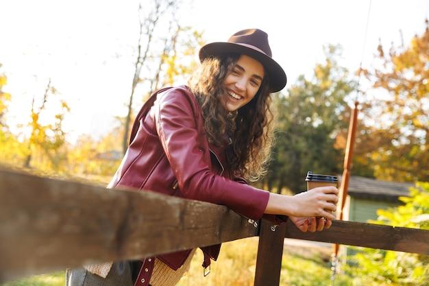 Красивая молодая женщина в шляпе, опираясь на деревянный мост в парке осенью, держит чашку кофе на вынос