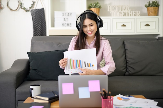 A beautiful young woman wearing headset is making video conference call via computer at home , business technology concept .