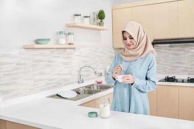 お茶を一杯に砂糖を追加するヒジャーブを着ている美しい若い女性