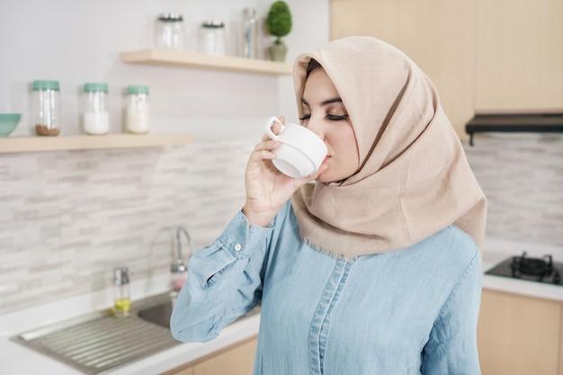 一杯のコーヒーを飲みながらヒジャーブを着ている美しい若い女性