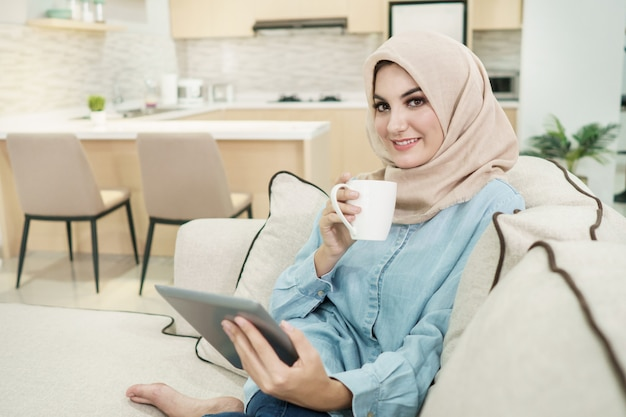 Beautiful young woman wearing hijab drinking a cup of tea while