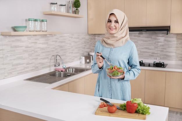 野菜のサラダを準備するヒジャーブを着ている美しい若い女性