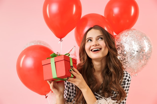 Beautiful young woman wearing a jacket standing isolated over pink background, celebrating, holding bunch of balloons and present box