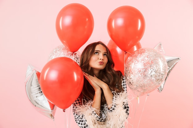 Beautiful young woman wearing a jacket standing isolated over pink background, celebrating, holding bunch of balloons