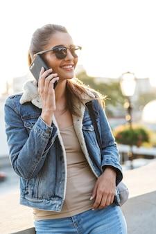 도시 거리에서 야외에서 걷고 재킷을 입고 아름 다운 젊은 여자, 휴대 전화에 복용